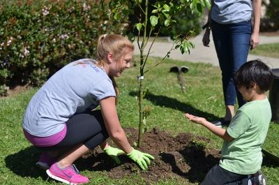 Lauren Wood with Child planting a tree